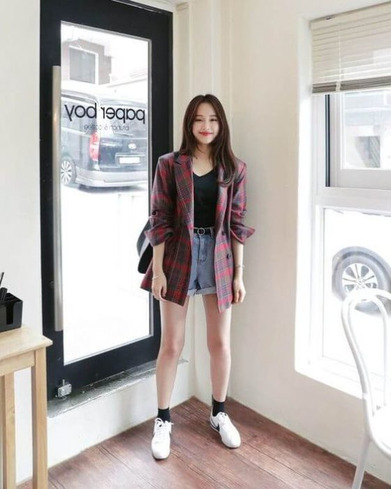 Asian girl with long black hair in black blouse, large plaid shirt on top of red color and denim shorts with white tennis shoes