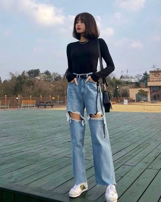Asian girl with short hair in long sleeve black blouse and ripped denim pants