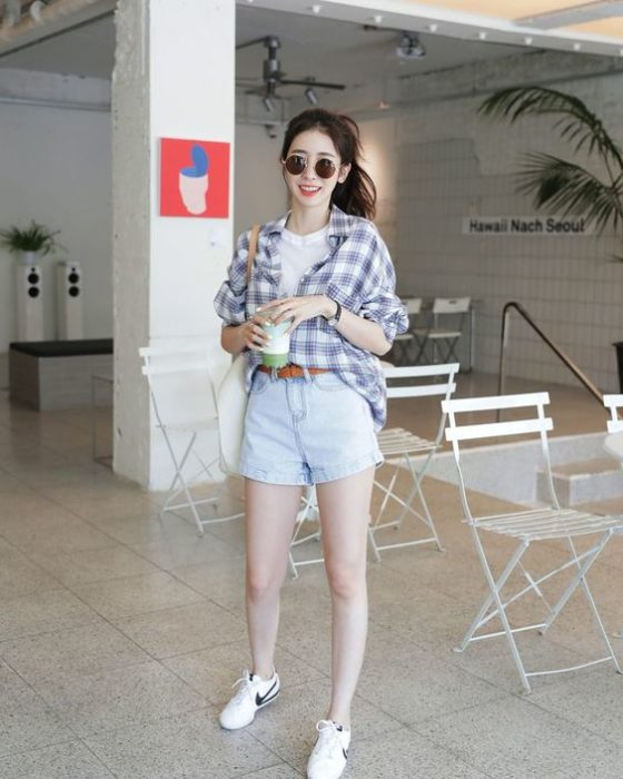 Long-haired Asian girl in a ponytail wears sunglasses, white blouse, plaid shirt, denim shorts and white tennis shoes
