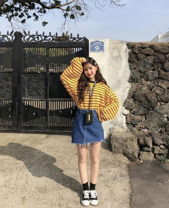 Asian girl with big yellow sweater with black stripes and denim skirt with black tape