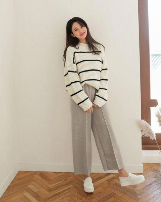 Asian girl with big white sweater with black stripes and wide gray pants