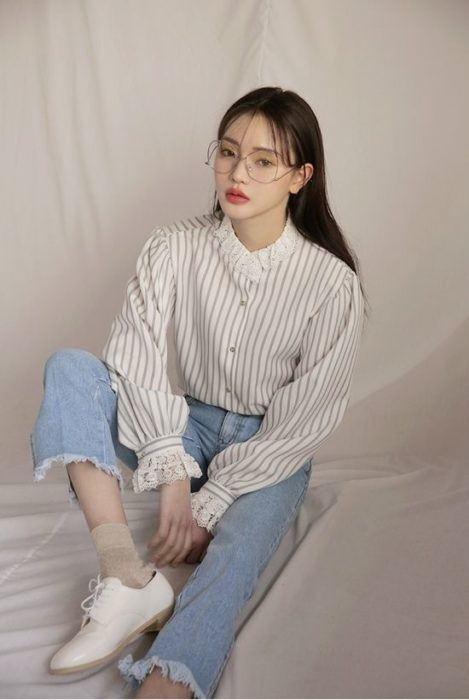 Asian girl sitting in white striped shirt and light blue jeans