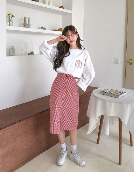 Asian girl in white sweater tucked in with long red skirt and white shoes