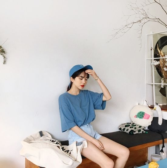 Asian girl sitting with blue cap and blouse and light denim shorts