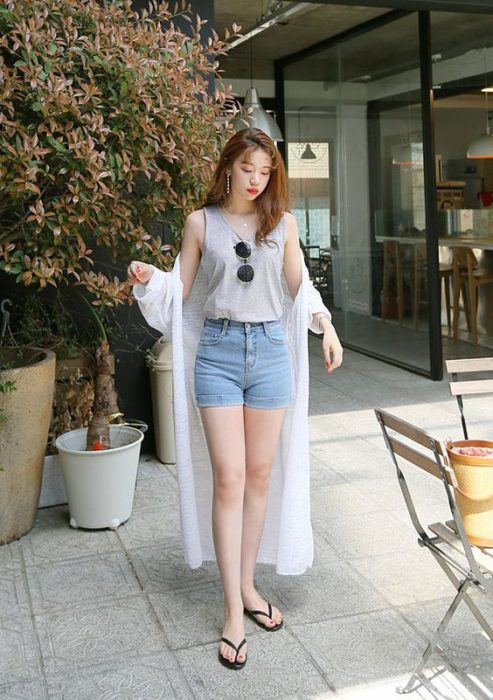 Asian girl with light loose hair wearing gray short-sleeved blouse, tucked in denim shorts and white kimono