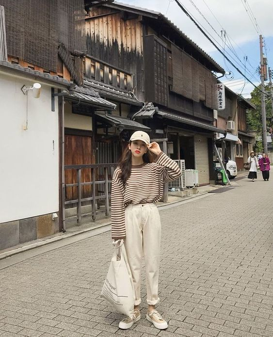 Asian girl with long hair wearing beige cap, beige long-sleeved blouse with brown stripes and oversized beige pants