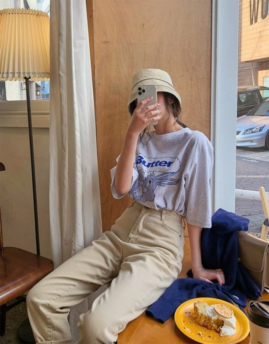 Asian girl sitting taking selfie with beige fish hat, oversized blue blouse and beige pants