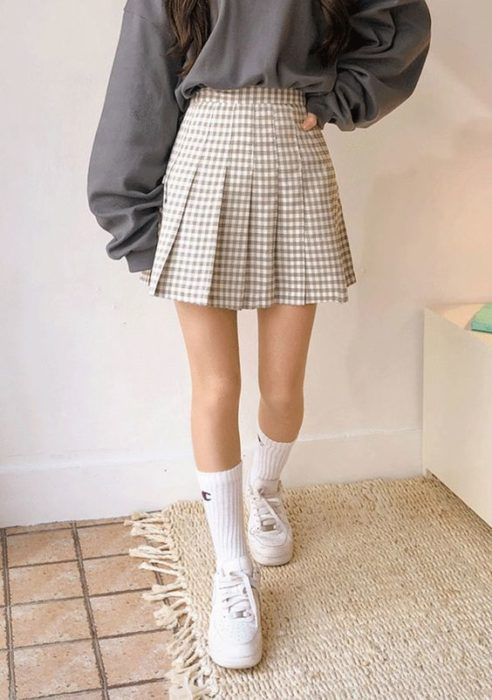 Asian girl in beige plaid skirt with plaid socks and white tape
