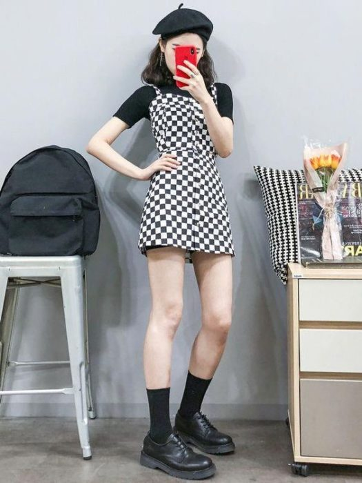 Asian girl takes selfie in front of the mirror with white short dress with black and black blouse underneath with black boots and hat
