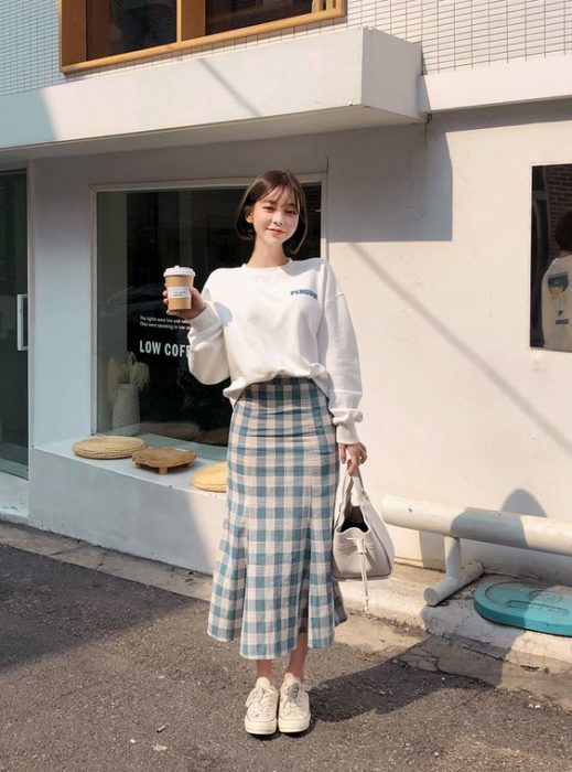 Short hair Asian girl wearing long plaid fake white sweatshirt and holding a coffee