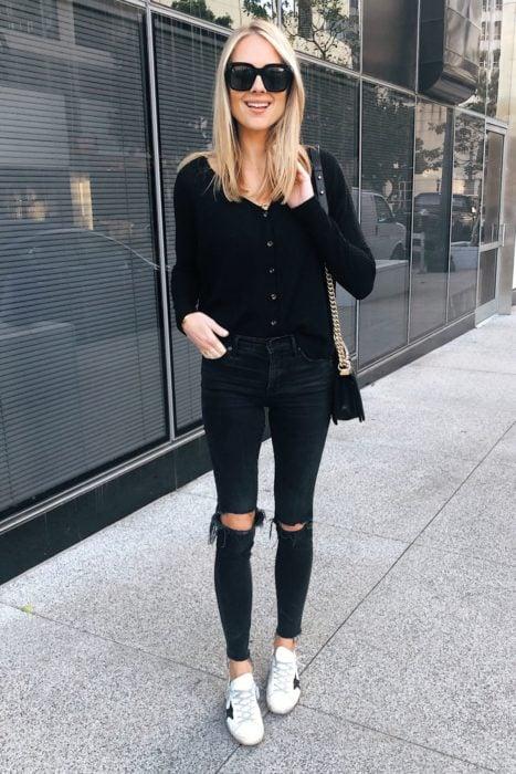 Chica usando jaens rasgados, blusa de manga larga en color negro y tenis blancos, además de lentes oscuros y bolso negro