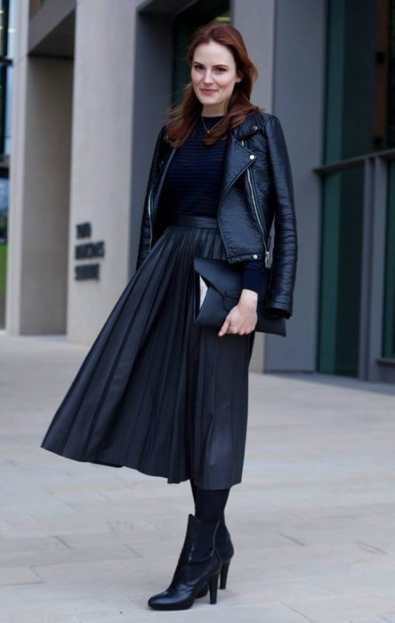 Girl wearing a black maxi skirt, ankle boots with tights of the same color, a blouse and leather jacket of the same color