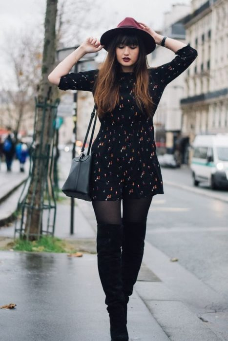 Girl wearing a total black look of stockings, 3/4 sleeve dress, short and hat