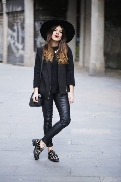 Girl wearing a total black look of leggings, blouse and leather jacket, hat and moccasin shoes with animal print