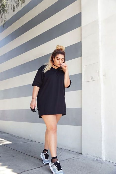Girl wearing a total black look of a short oversized short sleeve dress and tennis shoes