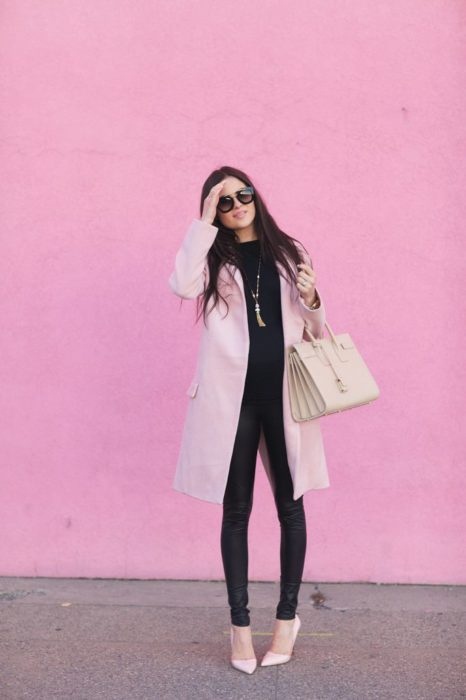 Girl wearing outfit with baby pink details in coat and bluza and black leggings