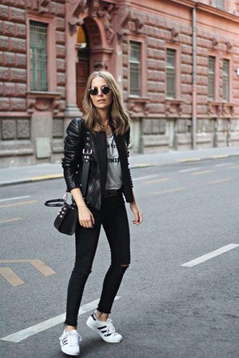 Chica usando chaqueta de cuero negra con jeans negros, y playera y tenis grises