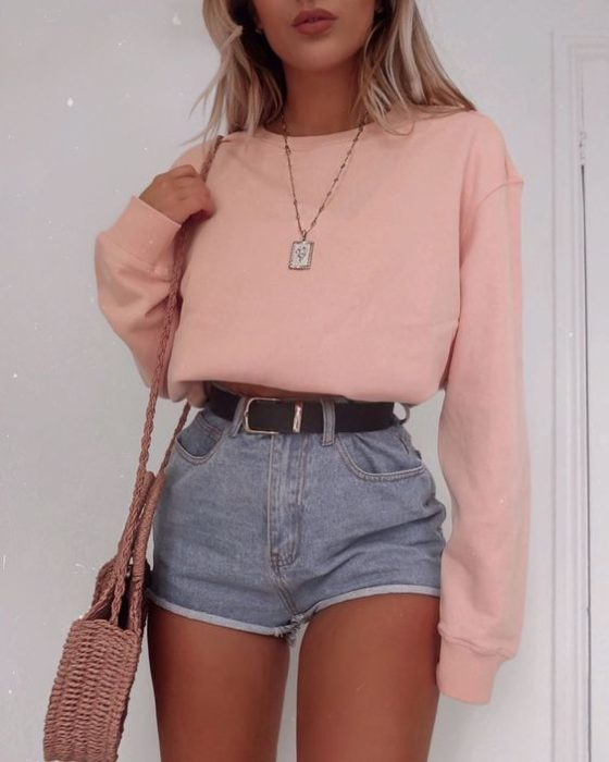 Girl wearing outfit with baby pink details in oversized sweatshirt and denim shorts with black belt