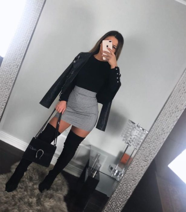 Girl wearing black leather jacket with high boots, gray skirt and black blouse