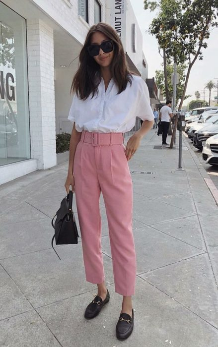 Girl wearing outfit with baby pink details in paper pants and white blouse, in addition to white shoes