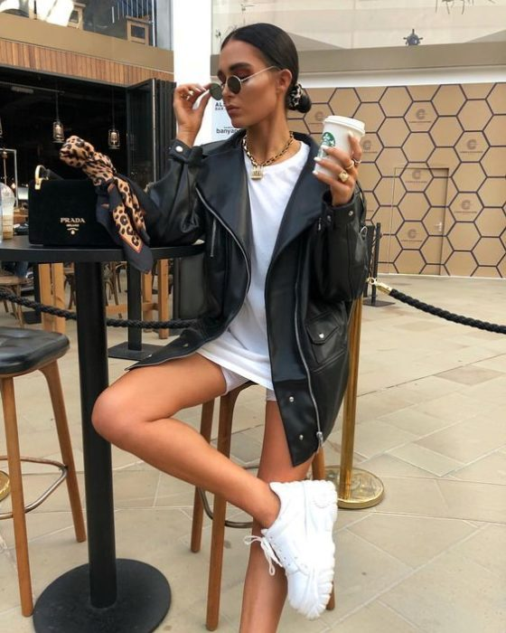 Girl wearing black leather jacket with oversized shirt and white tennis shoes