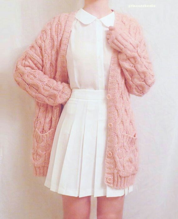 Girl wearing outfit with baby pink details in baggy loose knit sweater and white shirt and skirt