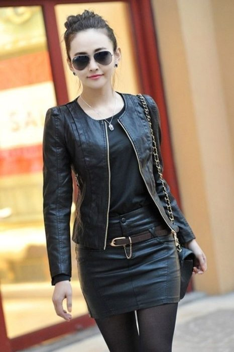 Chica usando chaqueta de cuero negra con falda de cuero y blusa negra