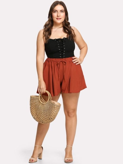 Girl wearing summer outfit of brick-colored casual shorts, black top, along with straw bag and heels