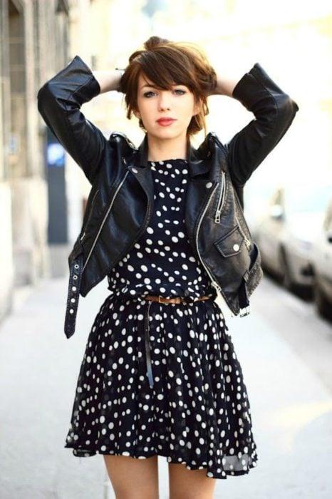 Chica usando chaqueta de cuero negra con vestido corto con lunares blancos