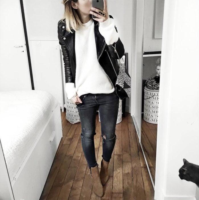 Chica usando chaqueta de cuero negra con jeans y suéter blanco holgado y botines color camel