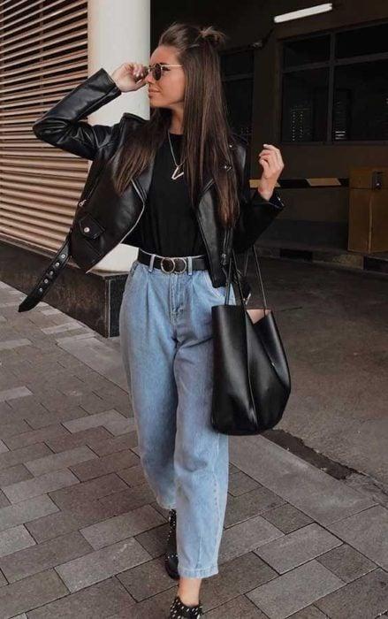 Chica usando chaqueta de cuero negra con mom jeans y blusa negra
