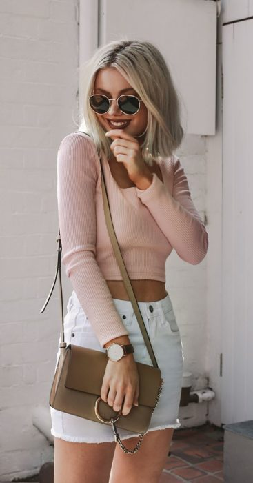 Girl wearing outfit with baby pink details in long sleeve blouse and white mini