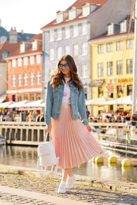 Girl wearing outfit with baby pink details in maxi skirt, white shirt and denim jacket