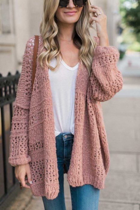 Girl wearing outfit with baby pink details in ensemble sweater, jeans and white blouse