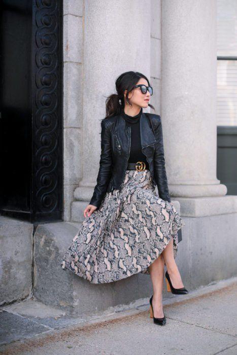Chica usando chaqueta de cuero negra con maxi falda de estampado y blusa negra