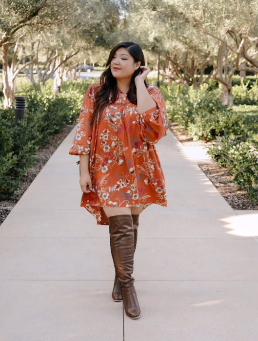 Girl wearing summer outfit of orange dress with print, 3/4 sleeves and brown high boots