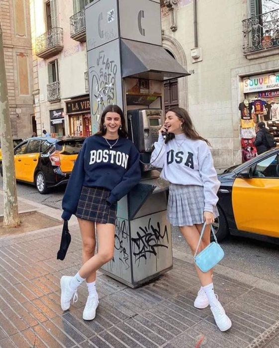 Chicas usando falda con estampado a cuadros y sudaderas holgadas