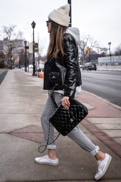 Chica usando chaqueta de cuero negra con pantal+ón gris, tenis blancos, y gorro blanco