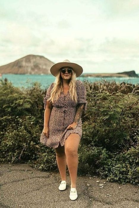 Girl wearing summer outfit of brown dress with buttons, white tennis shoes, sunglasses and straw hat