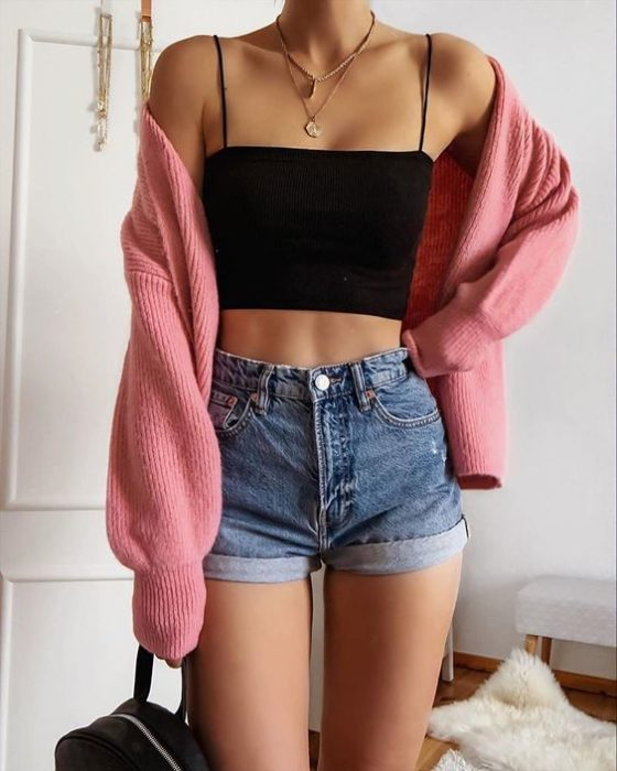 Girl wearing outfit with baby pink details in a loose sweater, and denim shorts as well as a black tank top