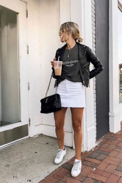 Girl wearing black leather jacket with skirt and white tennis shoes and gray baggy t-shirt