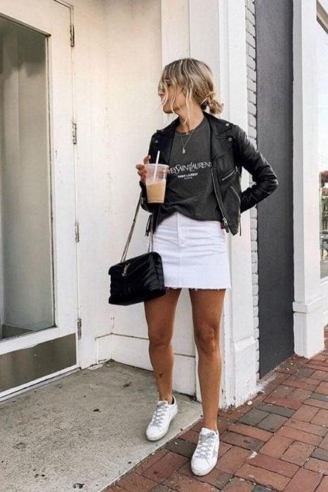 Chica usando chaqueta de cuero negra con falda y tenis blancos y playera holgada gris