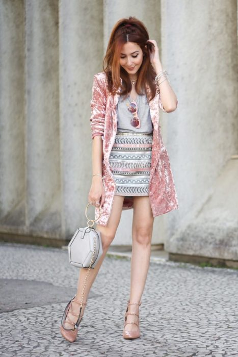 Girl wearing outfit with baby pink details in long velvet blazer