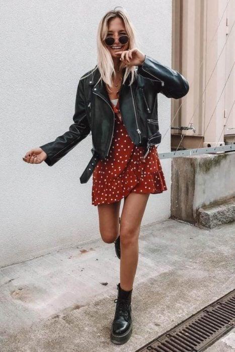 Chica usando chaqueta de cuero negra con vestido veraniego color ladrillo, y botines