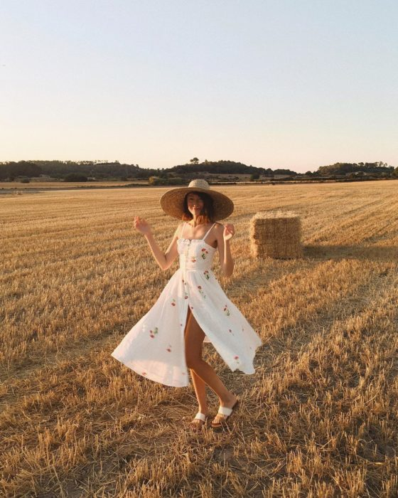 Girl wearing summer outfit of flared dress, white and print, and opening on one side and straw hat