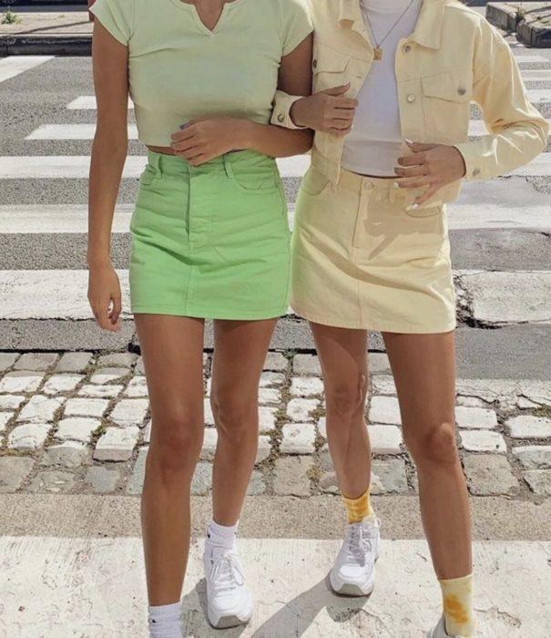 Chicas usando mini faldas y blusas en tonos verde y amarillo pastel