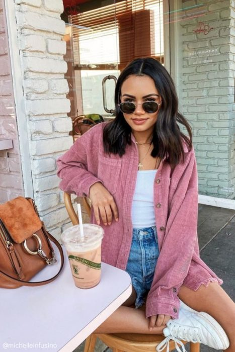 Girl wearing outfit with baby pink details in jacket, denim shorts and white blouse and tennis shoes