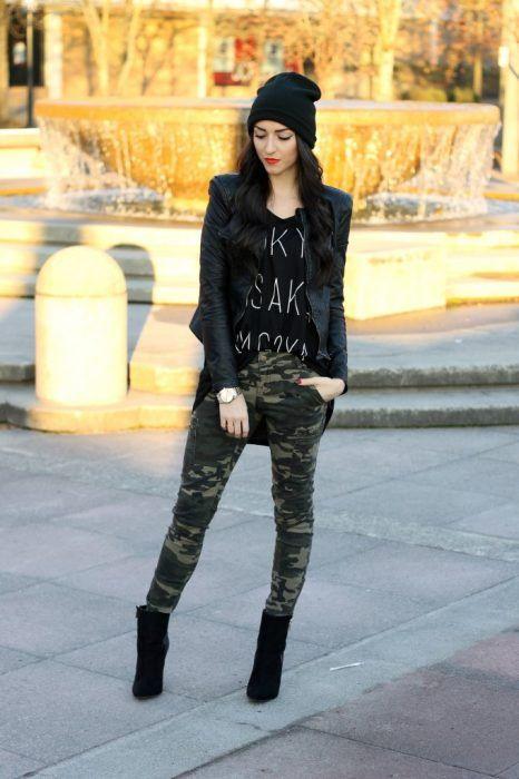 Chica usando chaqueta de cuero negra con botines negros, pantalón de estampado militar y blusa negra