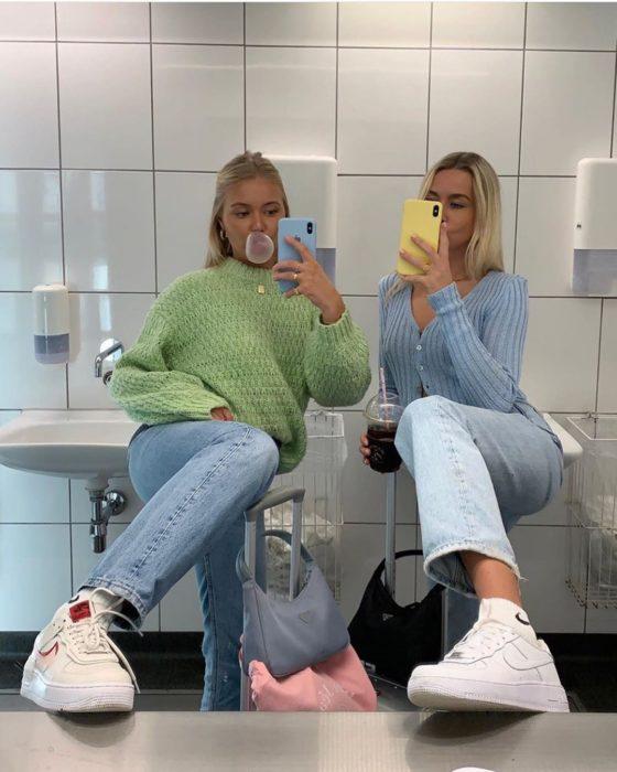 Chicas usando mom jeans y suéteres holgados verde y azul pastel