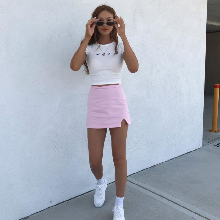 Girl wearing outfit with baby pink details in mini skirt and blouse and white tennis shoes